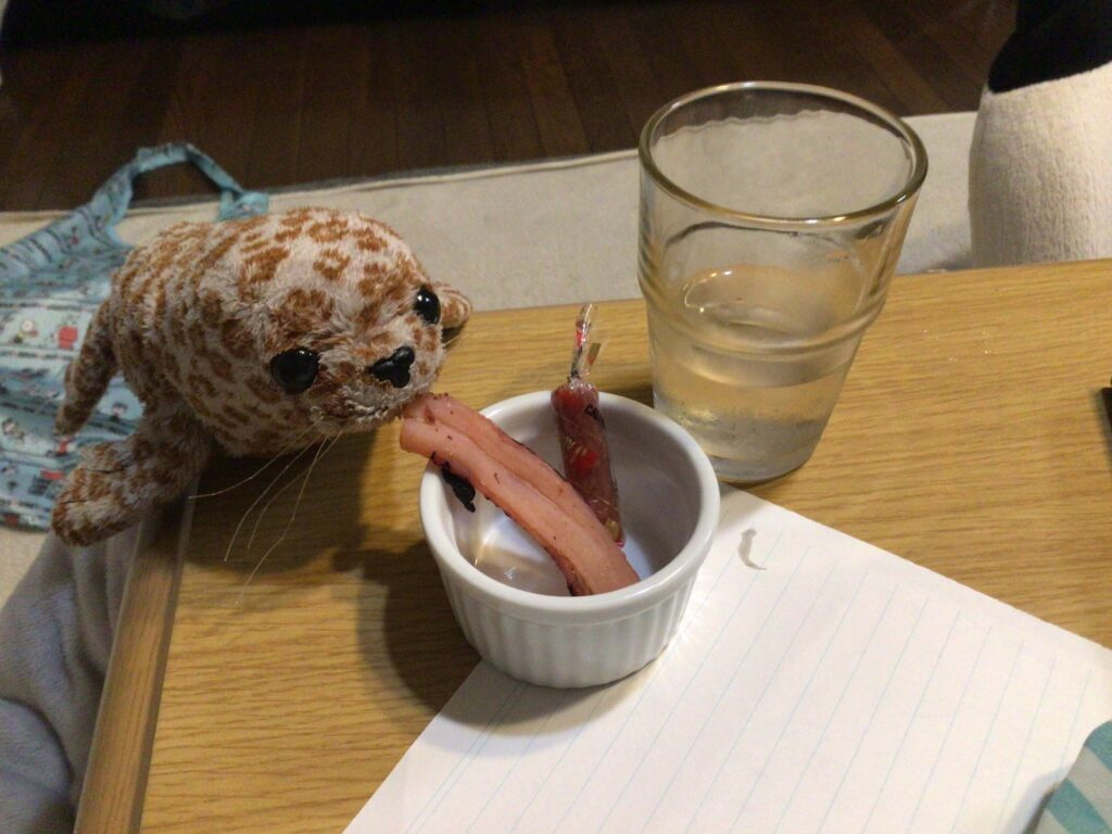 おつまみを食べるとつ先生の画像
